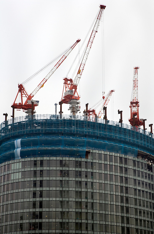 building of a big high rise with various cranes on top