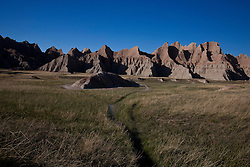 Hiking trail through grasslands leading to rock formations, Badlands National Park, South Dakota, United States of America