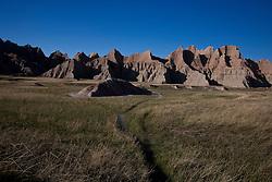 Hiking trail through grasslands leading to rock formations, Badlands National Park, South Dakota, United States of America