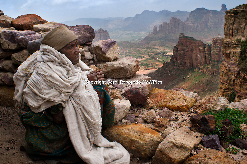 Gheralta mountains, near Hawzen, Eastern Tigray, Ethiopia. Nun of the Gheralta mountains. This nun carries on the top of the mountains of Gheralta from small, lives on what brings people with the steep of the area can no longer come down as the priest of the area. To visit one of about 30 churches built between the 14th and 16th century on the rocky walls of the area, it is best to spend at least a full day renting a car that will bring you to the different temples accompanied by a guide.