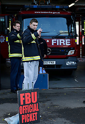 © Licensed to London News Pictures. 13/11/2013, London, UK.  Firefighters waves to a supporting horn from a passing vehicle as they picket outside Croydon fire station in south London in a four hour strike in a dispute over pensions, Wednesday, Nov. 13, 2013. Photo credit : Sang Tan/LNP