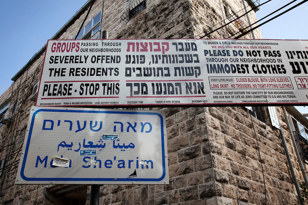 Sign posts at the perimeter of Mea Shearim call for visitors modesty in clothing and behaviour. Mea Shearim remains an Old World enclave in the heart of Jerusalem. The overwhelmignly Haredi population has preserved the traditional ways of life that existed for centuries among the Orthodox Jews of Eastern Europe. Life revolves around disciplined adherence to Jewish law, prayer and the study of Jewish texts. The residents follow strict dress and speech customs deriving from 17th century ghettos. Mea Shearim was established in 1874 as the second settlement outside the walls of the Old City.