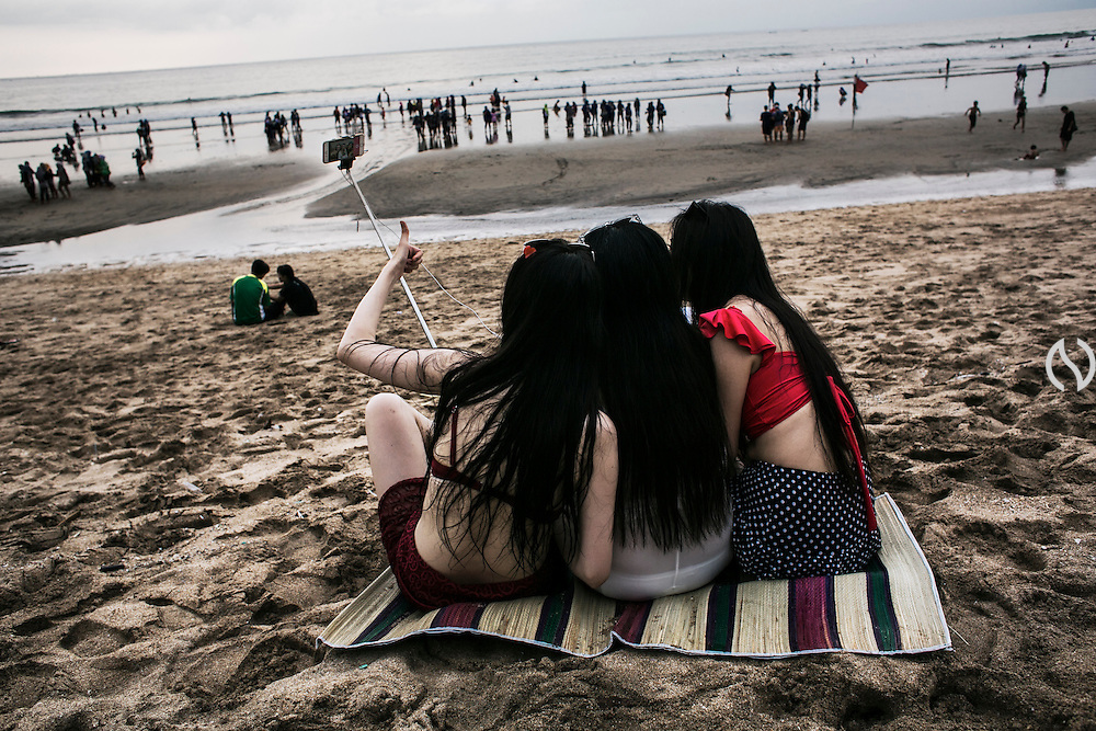 BALI, INDONESIA; APRIL 22, 2015: Tourists from China take a group selfie picture while on vacation in Kuta Beach, Bali, Indonesia on Wednesday, April 22, 2015.