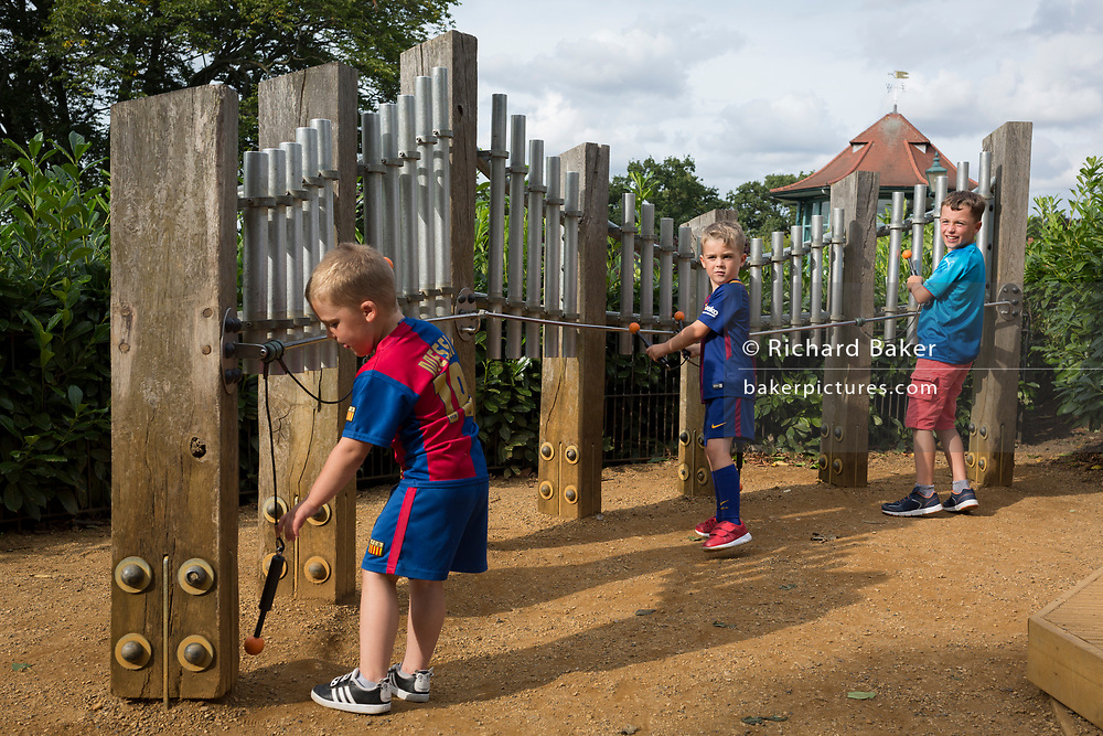 Young boys experiment with strike sound pipes to make musical notes in the Horniman Museum's Sound Garden, on 24th August 2017, Forest Hill, London, England.