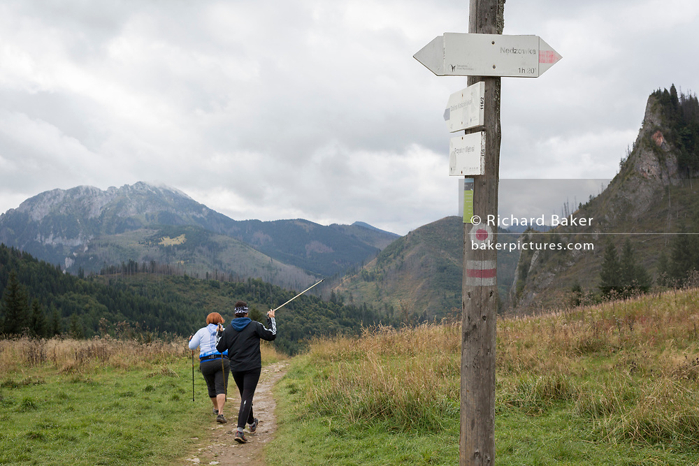 Two Polish walkers take the path straight ahead in the Tatra National Park, on 18th September 2019, in Dolina Mietusia, near Zakopane, Malopolska, Poland.