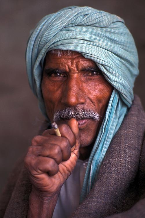 INDIA: Rajasthan.Portrait of man smoking bindi cigarette, Jodhpur