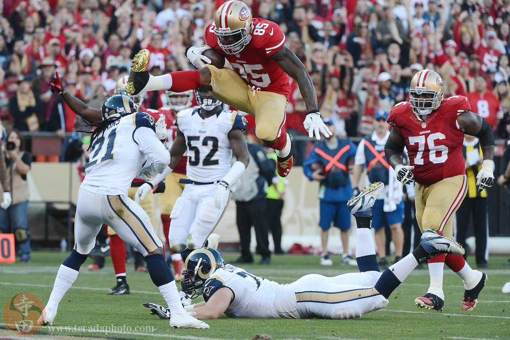 December 1, 2013; San Francisco, CA, USA; San Francisco 49ers tight end Vernon Davis (85) jumps over St. Louis Rams cornerback Janoris Jenkins (21) for a touchdown during the fourth quarter at Candlestick Park. The 49ers defeated the Rams 23-13.