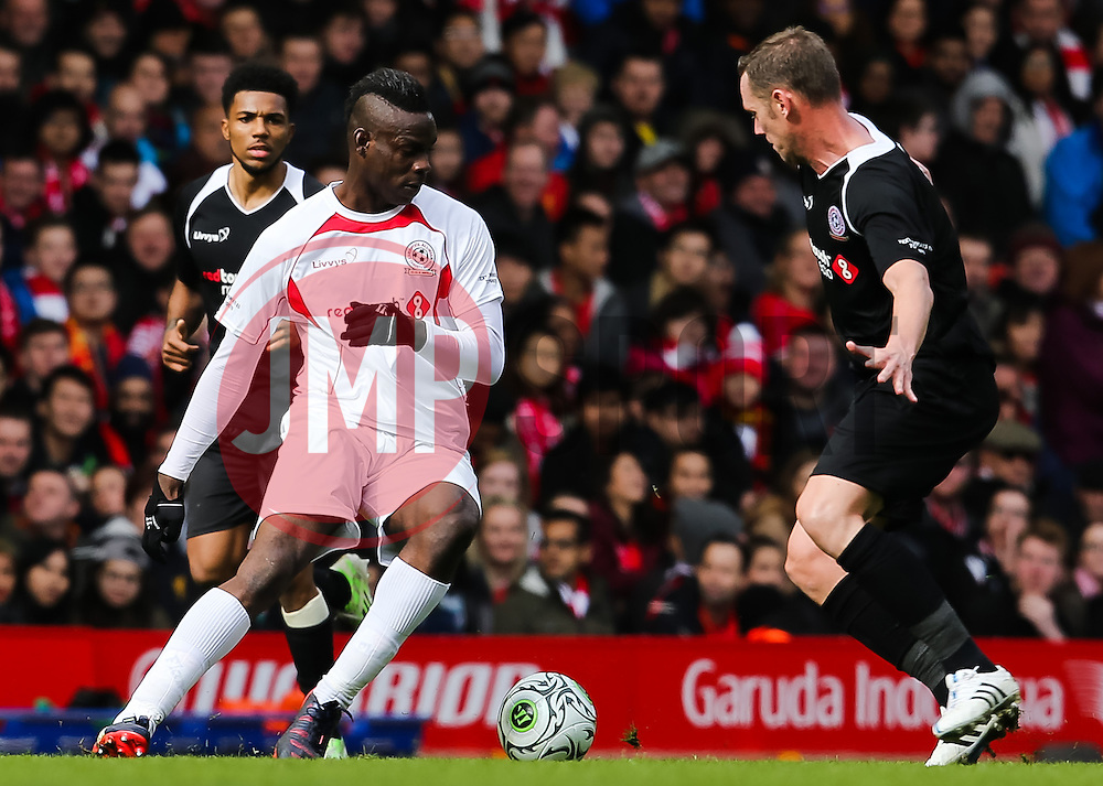 Mario Balotelli takes on Kevin Nolan - Photo mandatory by-line: Matt McNulty/JMP - Mobile: 07966 386802 - 29/03/2015 - SPORT - Football - Liverpool - Anfield Stadium - Gerrard's Squad v Carragher's Squad - Liverpool FC All stars Game