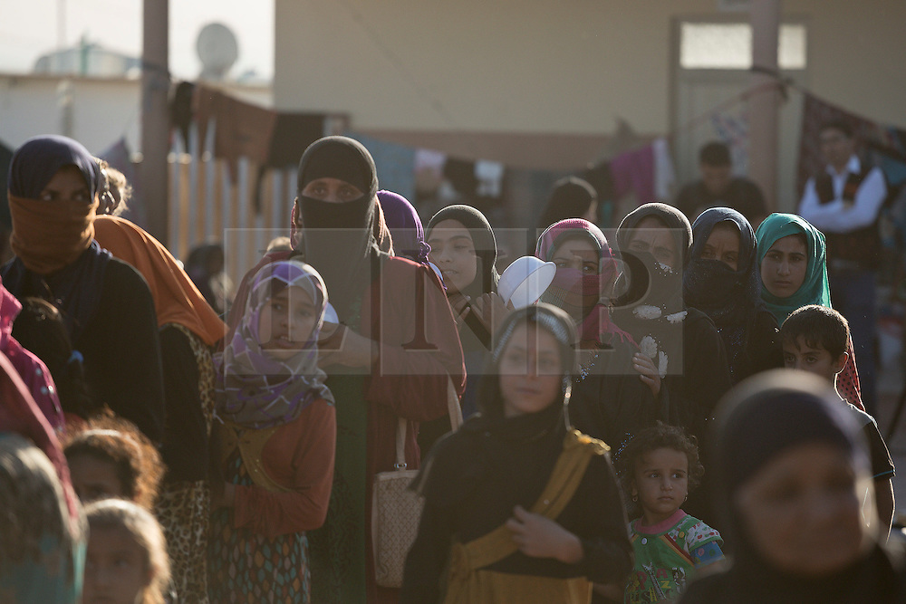 Licensed to London News Pictures. 22/10/2016. Female Iraqi IDPs, newly arrived from areas where the Mosul Offensive is taking place, queue for food served by aid workers in a school at the Dibaga refugee camp near Makhmur, Iraq. Upon arriving at the camp women and children stay in the school for around 10 - 15 days whilst completing the registration process.<br />