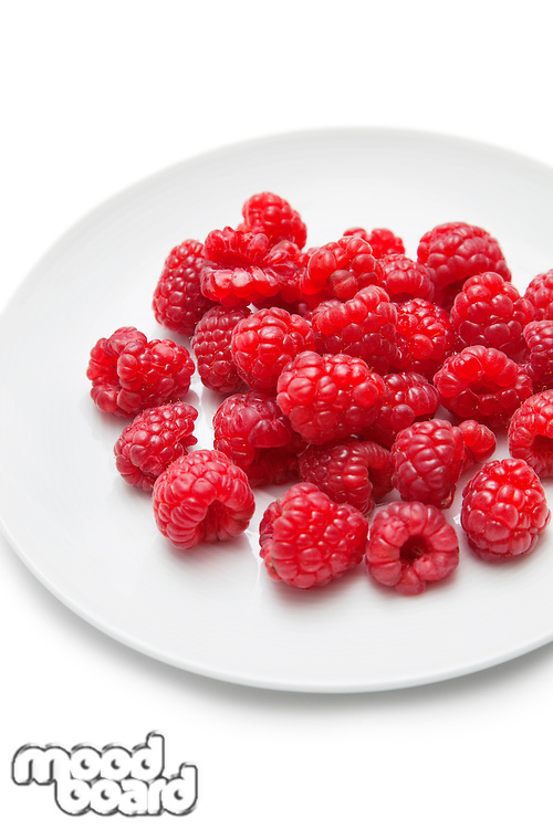 Fresh raspberries in plate against white background