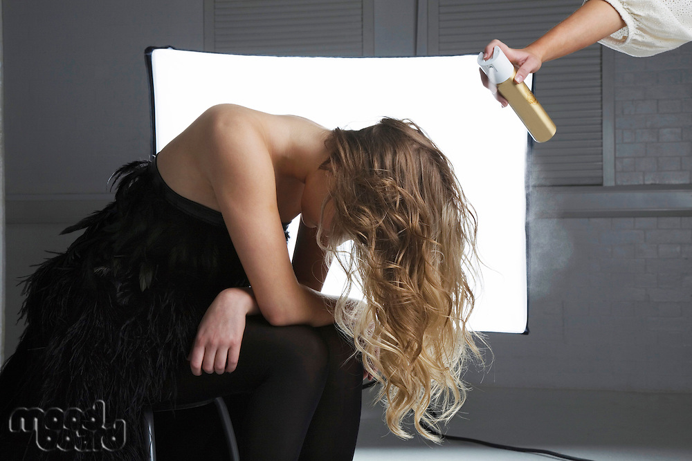 Hairstylist spraying hair product on model's hair
