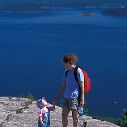 A mother and her young daughter on the summit of Champlain Mountain.  Frenchman Bay is in the distance.