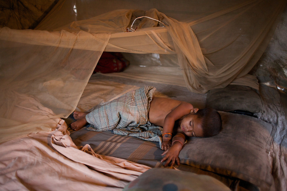 Sahera's youngest sister Shahida, age 2, sleeps, like the rest of the family, beneath a mosquito net. The net provides an escape from the incessant buzzing of flies that are everywhere in Shanti Busti. <br />