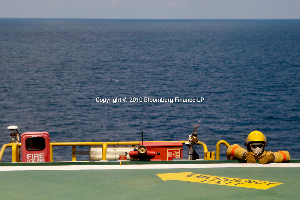 A worker on fire watch as a helicopter lands on board the Transocean Development Driller II rig leased by BP Plc which is drilling a backup relief well at the BP Plc Macondo well site in the Gulf of Mexico off the coast of Louisiana, U.S., on Saturday, August 7, 2010. BP successfully used the 'static kill', procedure  pumping mud into the top of the damaged well, BP plans now to finish a relief well to permanently plug the well by mid-August. Photographer: Derick E. Hingle/Bloomberg