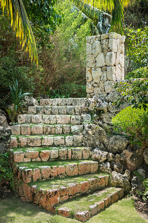 Coral stone steps, column and bronze bust sculpture in private landscaped garden at Cypress Pointe, Grand Cayman, Cayman Islands.<br /> <br /> Design by Alexander Urquhart