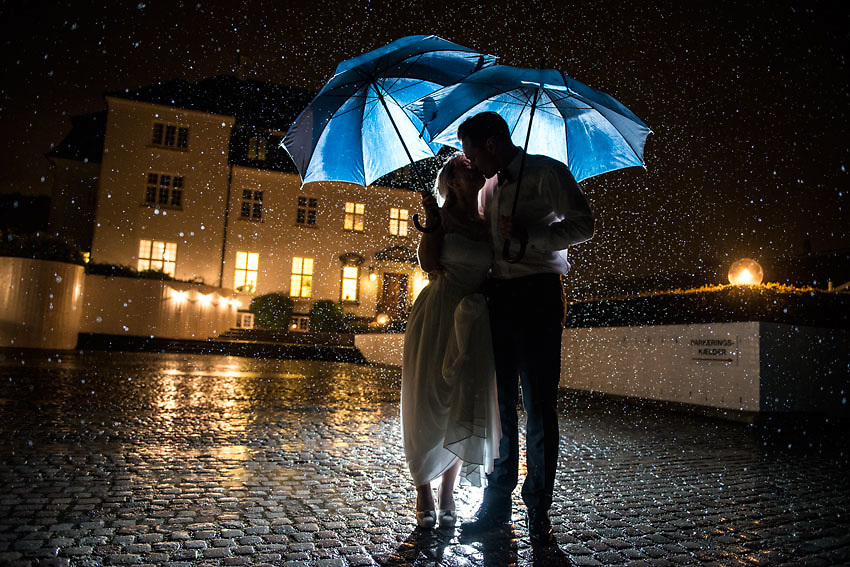 A wedding portrait photograph taken at night during heavy rain in Denmark