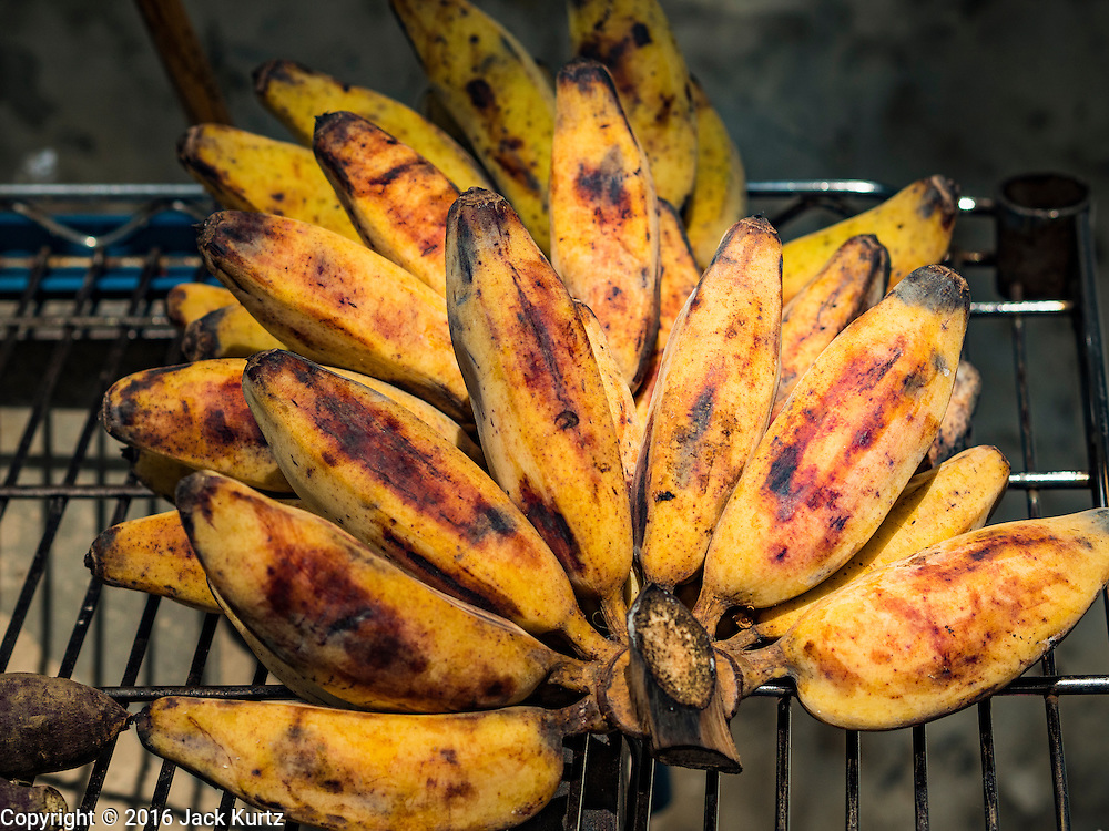 27 AUGUST 2016 - BANGKOK, THAILAND: Bananas on a grill during a lunch in the Pom Mahakan slum. The Pom Mahakan community is known for fireworks, fighting cocks and bird cages. Mahakan Fort was built in 1783 during the reign of Siamese King Rama I. It was one of 14 fortresses designed to protect Bangkok from foreign invaders. Only two of the forts are still standing, the others have been torn down. A community developed in the fort when people started building houses and moving into it during the reign of King Rama V (1868-1910). The land was expropriated by Bangkok city government in 1992, but the people living in the fort refused to move. In 2004 courts ruled against the residents and said the city could evict them. The city vowed to start the evictions on Sept 3, 2016, but this week Thai Prime Minister Gen. Prayuth Chan-O-Cha, sided with the residents of the fort and said they should be allowed to stay. Residents are hopeful that the city will accede to the wishes of the Prime Minister and let them stay.       PHOTO BY JACK KURTZ