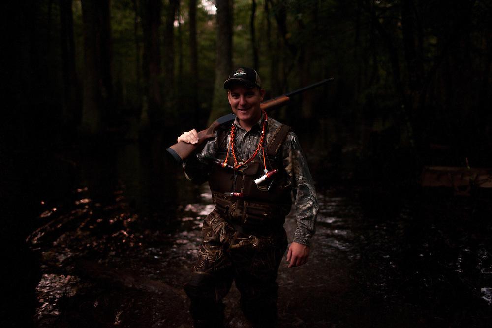 Duck hunter walking through swamp. Early morning sunrise.