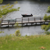 A boater cruises past a pier at Elvis Presley Lake as he heads for the boat ramp to leave the lake for the day.