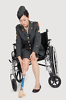 Female US military officer in wheelchair fitting prosthesis foot over gray backgrounds