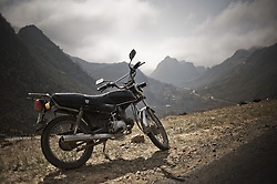 A motorbike is parked along a road with mountainous landscape in background. Ha Giang province, Vietnam, Asia
