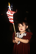 A young Korean girl waves an American flag during an immigration naturalization ceremony November 12, 1996 in Washington, DC.