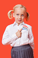 Portrait of a young school girl with vote badge over orange background