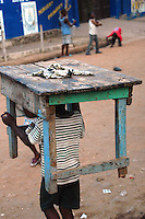 GHANA,Accra,Jamestown, 2007. A young businessman moves shop to a different place along Jamestown's seaside strip.