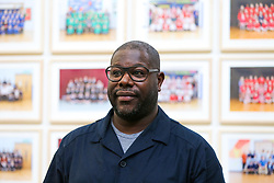 © Licensed to London News Pictures. 11/11/2019. London, UK.Turner Prize-winning artist and Oscar-winning filmmaker Steve McQueen poses for photograph at the preview of his Year 3 exhibition at Tate Britain. An installation of over 3,000 class photographs lining the walls of Tate Britain's Duveen Galleries, depicting more than 70,000 Year 3 pupils from London's primary schools.The exhibition opens on 12 November until 3 May 2020. Photo credit: Dinendra Haria/LNP