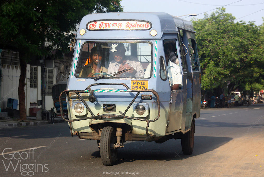 Indian tricycle motor rickshaw bus rushes through city streets of Pondicherry. India