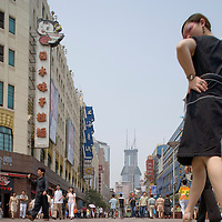 Asia, China, Shanghai, Young woman peers over her shoulder while walking through retail shopping and restaurant district lining Nanjing Road on summer morning.