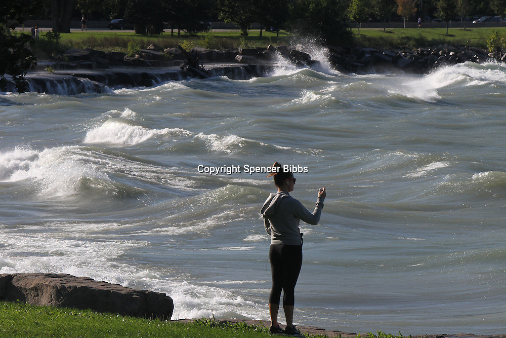 """A young woman takes time to photograph the waves on Lake Michigan at The Point during a windy day Saturday afternoon.<br /> <br /> Please 'Like' """"Spencer Bibbs Photography"""" on Facebook.<br /> <br /> All rights to this photo are owned by Spencer Bibbs of Spencer Bibbs Photography and may only be used in any way shape or form, whole or in part with written permission by the owner of the photo, Spencer Bibbs.<br /> <br /> For all of your photography needs, please contact Spencer Bibbs at 773-895-4744. I can also be reached in the following ways:<br /> <br /> Website – www.spbdigitalconcepts.photoshelter.com<br /> <br /> Text - Text """"Spencer Bibbs"""" to 72727<br /> <br /> Email – spencerbibbsphotography@yahoo.com"""