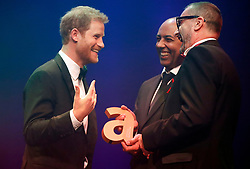 Prince Harry (left) receives a posthumous Legacy award on behalf of his mother Diana, Princess of Wales, from Ian Walker, (right) and Julian La Bastide, at the Attitude Awards in London.