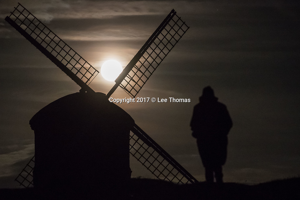 "Chesterton, Warwickshire, UK. 3rd December 2017. The so called ""Cold"" supermoon rises above the eastern horizon at Chesterton. The Warwickshire village is home to the striking Grade 1 listed Chesterton Windmill, built in 1632 from a design attributed to Inigo Jones, just off the Fosse Way. Pictured: A woman makes her way towards the windmill. // Lee Thomas, Tel. 07784142973. Email: leepthomas@gmail.com  www.leept.co.uk (0000635435)"