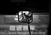 A bus driver is seen in a rearview mirror in Chongqing.