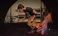 12/10/2014 MILLBURY Framed by his forge, Blacksmith Derek Heidemann hammers out a nail.