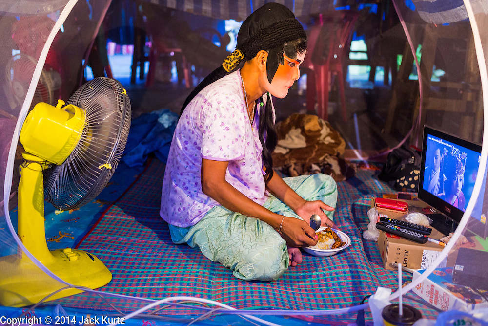 "19 AUGUST 2014 - BANGKOK, THAILAND:  A performer with the Lehigh Leng Kaitoung Opera troupe eats dinner in her mosquito net tent while she watches a Chinese opera on her computer before a performance at the Chaomae Thapthim Shrine, a small Chinese shrine in a working class neighborhood of Bangkok. The performance was for Ghost Month. Chinese opera was once very popular in Thailand, where it is called ""Ngiew."" It is usually performed in the Teochew language. Millions of Chinese emigrated to Thailand (then Siam) in the 18th and 19th centuries and brought their culture with them. Recently the popularity of ngiew has faded as people turn to performances of opera on DVD or movies. There are still as many 30 Chinese opera troupes left in Bangkok and its environs. They are especially busy during Chinese New Year and Chinese holiday when they travel from Chinese temple to Chinese temple performing on stages they put up in streets near the temple, sometimes sleeping on hammocks they sling under their stage. Most of the Chinese operas from Bangkok travel to Malaysia for Ghost Month, leaving just a few to perform in Bangkok.        PHOTO BY JACK KURTZ"
