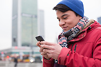 Smiling man using cell phone in city during winter