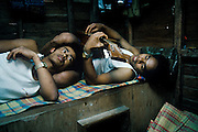 Abanteros, young gold miners, relax by playing music in the shared cupboard that is their home, Mount Diwata, Mindanao, The Philippines