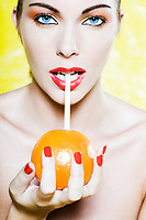 beautiful caucasian woman portrait drinking orange juice with a straw studio on yellow background
