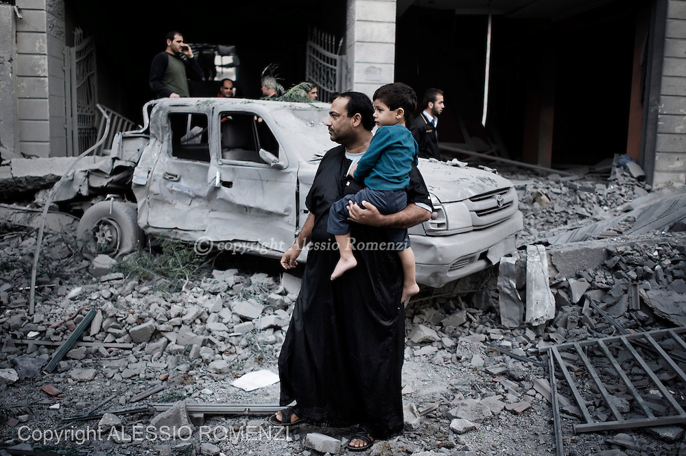 Gaza City: Palestinians stand in front of a building damaged by airstrike in Gaza City. November 19, 2012. ALESSIO ROMENZI