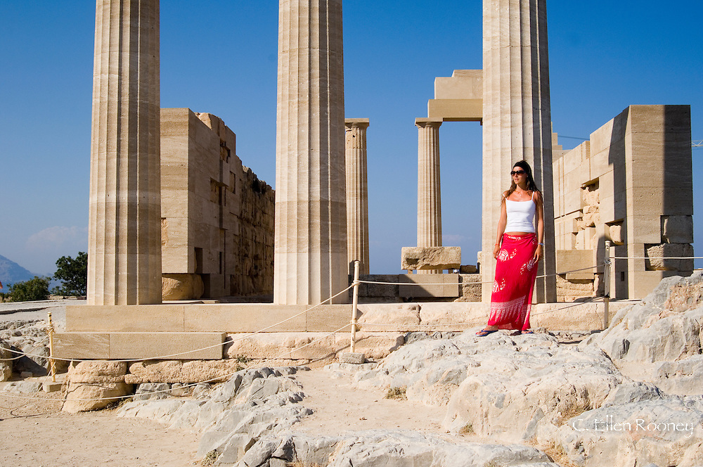 A woman posing for a photograph at a ruined temple at The Acropolis, Lindos, Rhodes, Dodecanese Islands,  Greece
