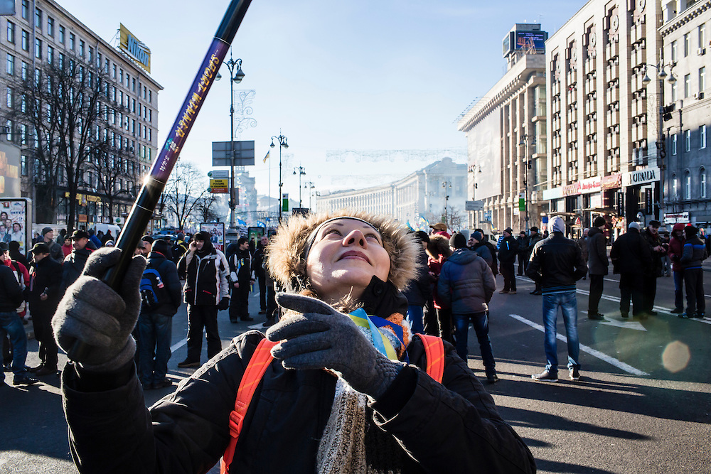 KIEV, UKRAINE - DECEMBER 14: Sveta Chusova, an anti-government protester, waves a flag near Independence Square on December 14, 2013 in Kiev, Ukraine. Thousands of people have been protesting against the government since a decision by Ukrainian president Viktor Yanukovych to suspend a trade and partnership agreement with the European Union in favor of incentives from Russia. (Photo by Brendan Hoffman/Getty Images) *** Local Caption *** Sveta Chusova