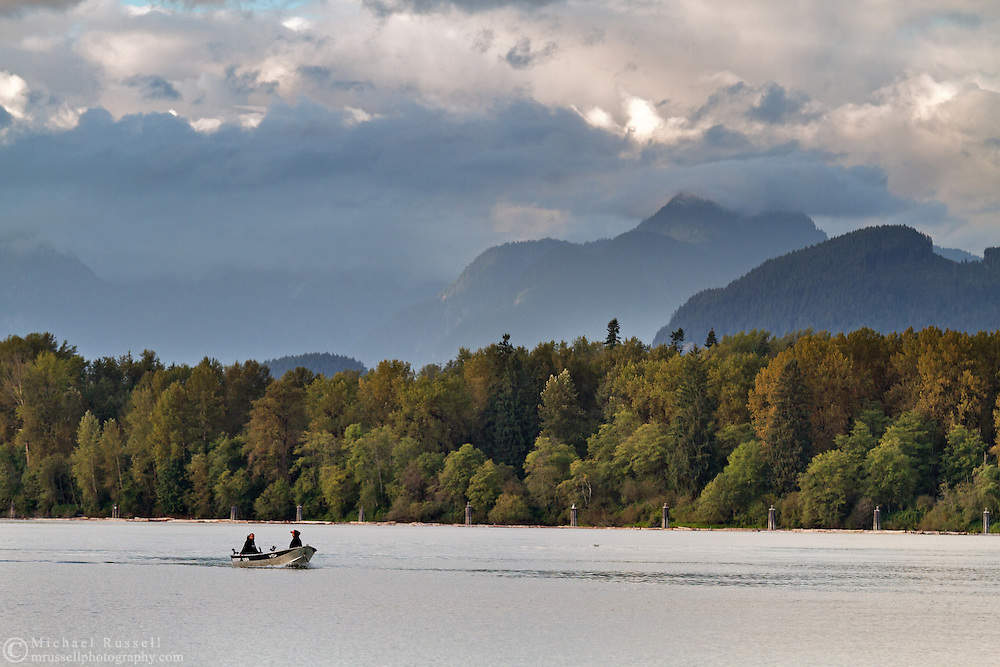 Two fisherman in an aluminum boat in the Fraser River at Fort Langley, British Columbia, Canada.  Photographed from Tavistock Point in Brae Island Regional Park.