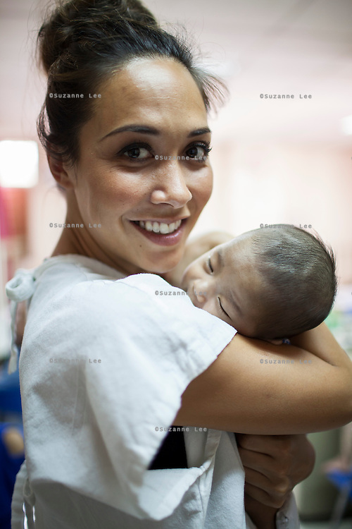 Myleene Klass, a high profile UK celebrity, TV host, violinist and pianist, holds 2-month-old John Darwin Tagyam, who has pneumonia, in the Florencio V. Memorial Hospital in Paranaque city, Metro Manila, The Philippines on 19 January 2013. Photo by Suzanne Lee for Save the Children UK