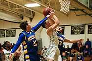 Winooski's Brandon Bigelow (5) leaps between Milton's Joseph Beaupre (31) and Kyle Apgar (33) for a lay up during the boys basketball game between the Milton Yellowjackets and the Winooski Spartans at Winooski High School on Tuesday evening December 29, 2015 in Winooski. (BRIAN JENKINS/for the FREE PRESS)