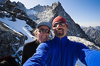 A active couple taking a self portrait with mountains in the background, Enchantment Lakes Wilderness Area, Washington Cascades, USA.