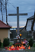 Young girl lighting a candle under a large stone cross outside the Bone Chapel at Kudowa Zdroj, Poland.