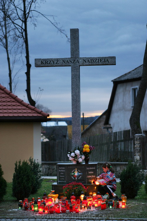 Young girl lighting a candle under a large stone cross outside the Bone Chapel at Kudowa Zdroj, Poland.