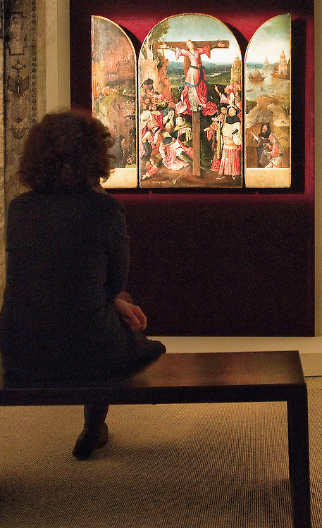 "VENICE, ITALY - JANUARY 10:  A member of staff admires ""Triptych of the Martyrdom of St Liberatal"" panels by Hieronymus Bosch on display at Palazzo Grimani on January 10, 2011 in Venice, Italy. The  exhibition will be open until 20th March 2011."